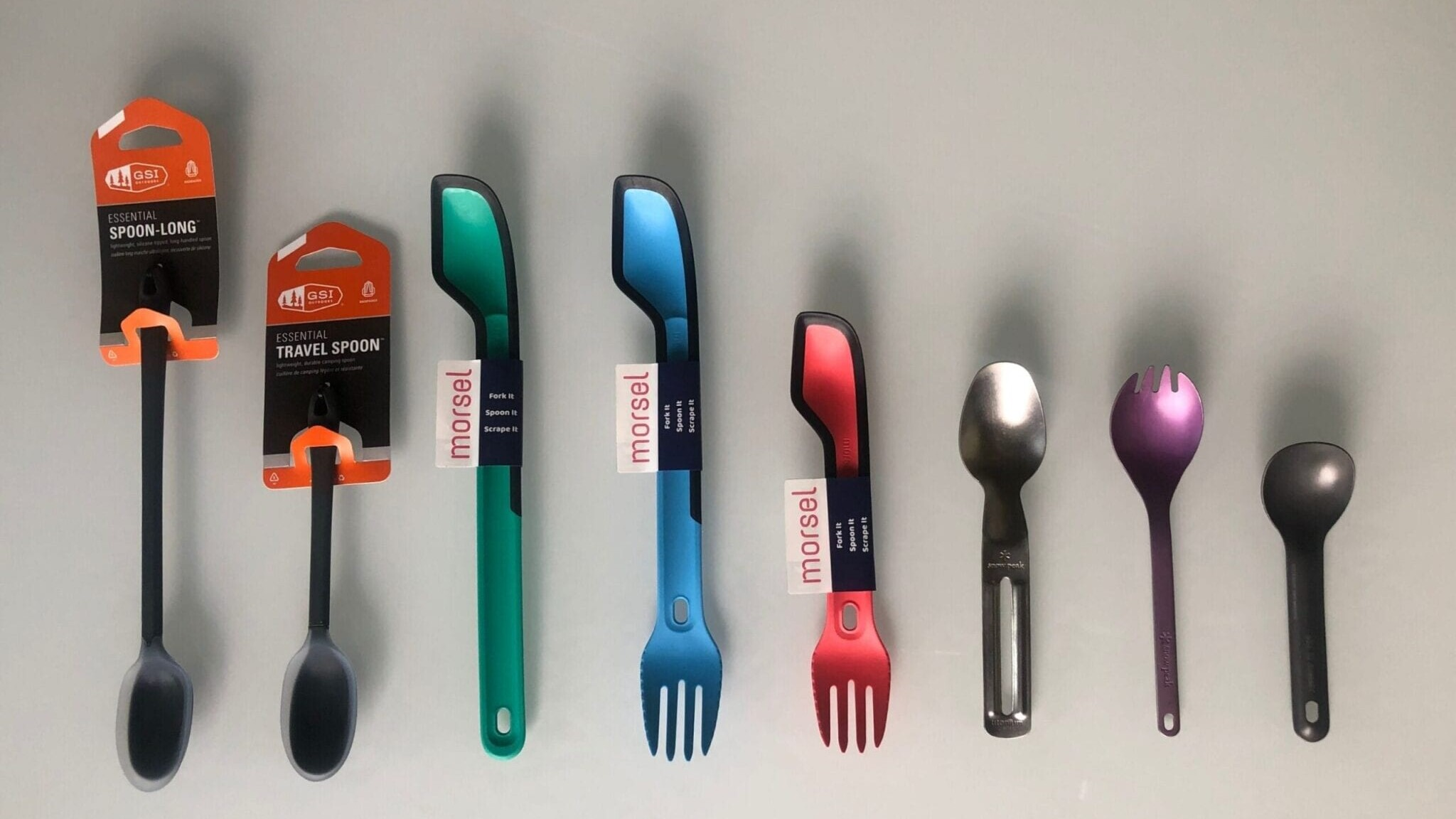 A variety of backpacking spoons in a line on a table.