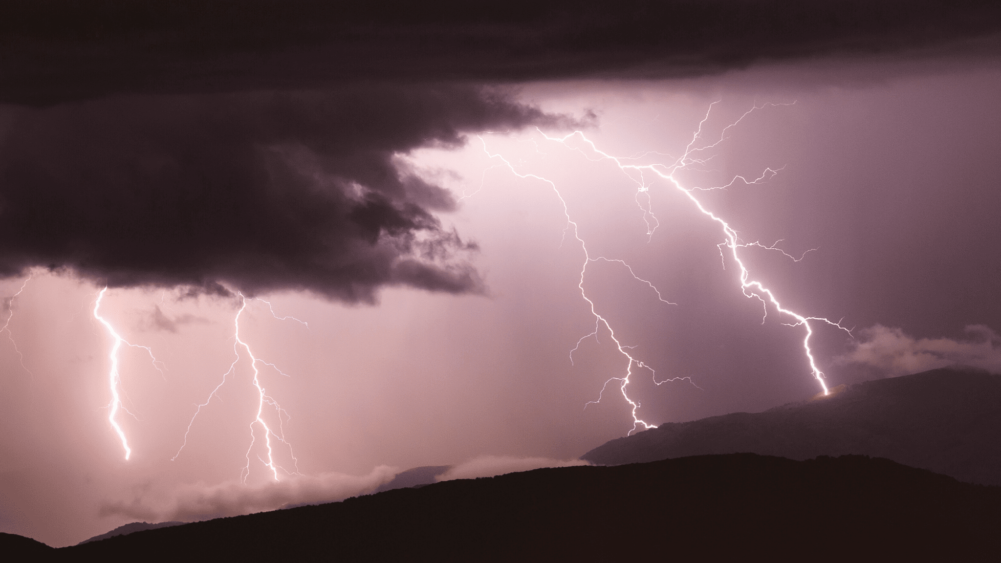 Four lightning strikes on a dark and flat mountain.