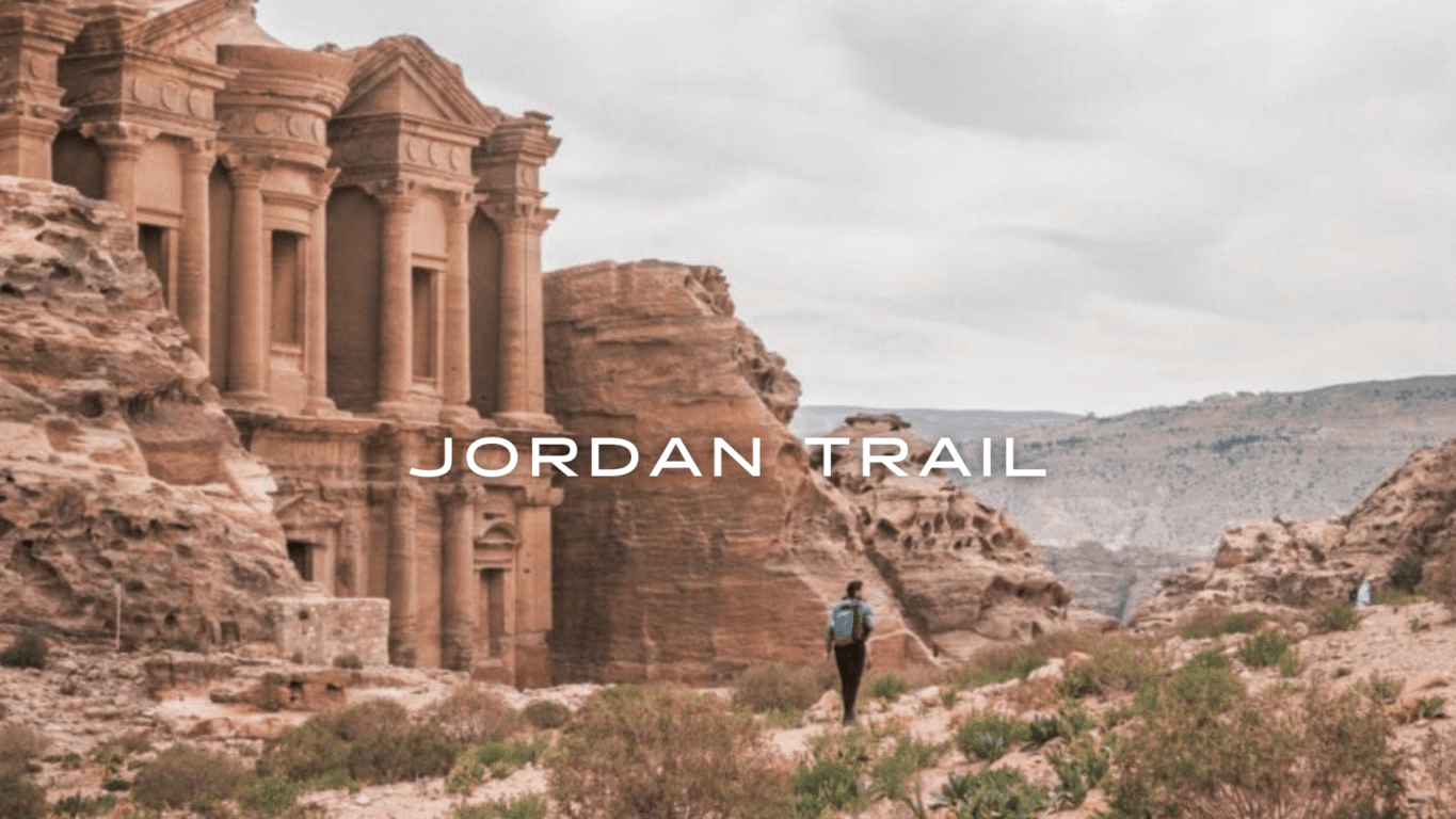 A hiker walks through a desert landscape near a historic structure.