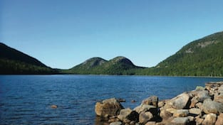 A lake with green hills in the background, located at Acadia National Park